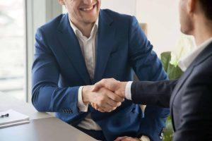 Men shaking hands, man in blue uses the proper etiquette