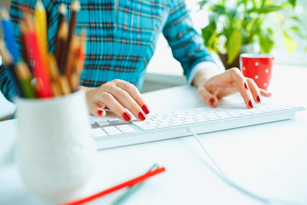 Woman writing blogs on a keyboard