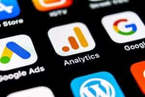 Mobile phone with the apps for google analytics, google ads, and google showing in a mobile ad.