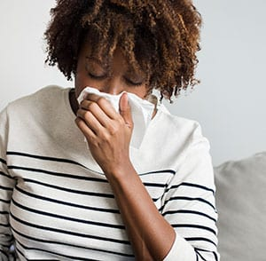 Black female coughs into tissue